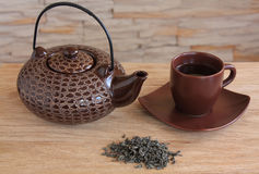 Brown teapot and cup with green tea Stock Photos