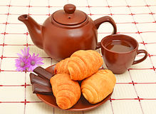 Brown teapot, cup and sauser with croissant. And chocolate Royalty Free Stock Photography