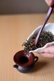 Brown teapot. Filling a brown teapot through a funnel Stock Photo