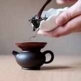 Brown teapot. Filling a brown teapot through a funnel Stock Photos