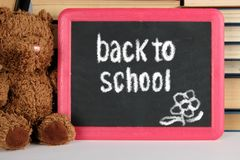 Brown teddy bear and black board in red frame. Brown teddy bear and  black board in red frame on the background of pile of books, concept back to school royalty free stock photo