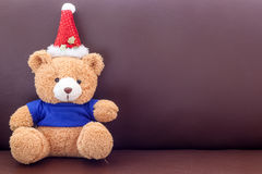Brown teddy bear with blue shirt wearing christmas hat on the sofa Royalty Free Stock Photos