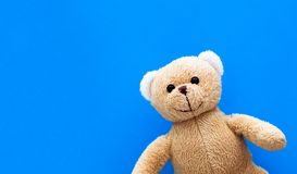 Brown teddy bear child toy isolated in a seamless pastel blue coulor with large empty space background stock photo