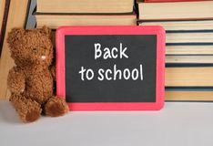 Brown teddy bear and empty black board in red frame. On the background of pile of books, concept back to school royalty free stock photography