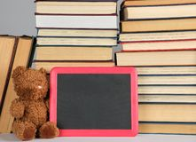 Brown teddy bear and empty black board in red frame on the background of pile of books. Concept back to school, copy space stock image