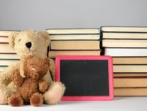 Brown teddy bear and empty black board in red frame on the background of pile of books. Concept back to school, copy space royalty free stock images