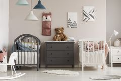 Brown teddy bear on grey wooden commode between two cribs in fashionable bedroom for twins. Brown teddy bear on grey wooden commode between two cribs in stock photos