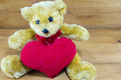 Brown teddy bear hugging a big red heart Royalty Free Stock Images
