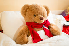 Brown teddy bear in read scarf lying in bed with thermometer Royalty Free Stock Image