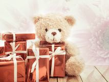 Brown teddy bear with red gift box. On blur gerbera flower background, Christmas and New year concept Stock Photo