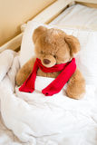 Brown teddy bear in red scarf lying in bed under blanket Stock Photos