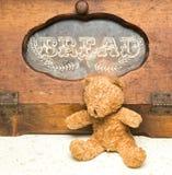 Brown Teddy Bear Sitting davanti ad un vecchio contenitore di pane fotografia stock libera da diritti