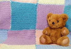 Teddy bear on a knitted background. Brown teddy bear, teddy bear on a knitted background, knitted squares, knitted plaid of squares, multicolored background, an royalty free stock photos
