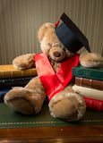 Brown teddy bear wearing graduation cap leaning on books Stock Photo