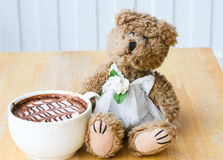 Brown teddy bear in wedding dress with a hot coffee mocha in pastel tone background. Royalty Free Stock Photo