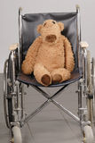 Brown teddy bear in wheelchair Royalty Free Stock Images