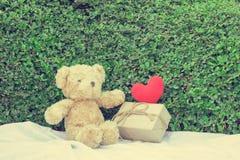 Brown-Teddybär, der auf weißem Gewebe sitzt Stockbild
