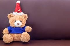 Brown-Teddybär mit tragendem Hut des blauen Hemdes Weihnachtsauf dem Sofa Lizenzfreie Stockfotos