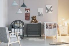 Brown-Teddyb?r betreffen graue h?lzerne Kommode zwischen zwei Krippen im modernen Schlafzimmer f?r Zwillinge stockbilder