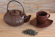 Brown-Teekanne und Cup mit grünem Tee Stockfotos
