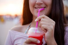 Brown teenage girl drinks an icy red drink royalty free stock images