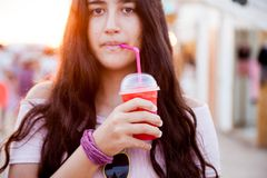 Brown teenage girl drinks an icy red drink stock images