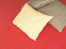 Brown textile pillows on the red floor. Royalty Free Stock Photography