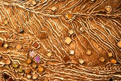 The brown texture of the concrete wall is made of decorative plaster with the addition of multi-colored gems, glass squares and ci. Rcles with veins and patterns Royalty Free Stock Photos