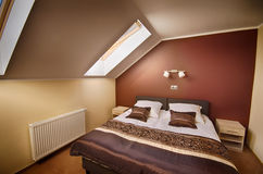 Brown theme loft bedroom. Elegant and simple double bed brown theme bedroom with natural daylight coming from the window. Loft room Royalty Free Stock Photos