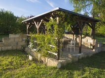 Free Brown Tiber Wooden Gazebo Or Pergola With Climbing Plants And Fl Stock Image - 118123321