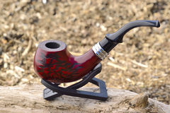 A brown tobaco pipe. On alogg Stock Photography