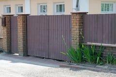 Brown-Tor und Teil eines Zauns hergestellt von der Metall- und Ziegelsteinaußenseite in der grünen Vegetation lizenzfreies stockbild