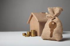 Brown torba z kluczowym logo Złociste monety i domowego papieru dom Pojęcie wynajmowania i kupienia dom zdjęcie royalty free