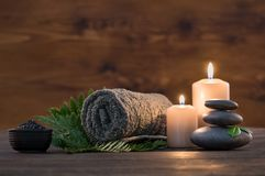 Spa treatment set. Brown towel on green fern with candles and black hot stone on wooden background. Hot stone massage setting lit by candles. Hot stone therapy stock photos