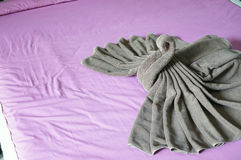 Brown towel plait as swan on pink bed Royalty Free Stock Photo