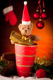 Brown toy bear with christmas gifts over warm brown background Stock Photo
