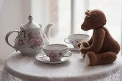 Brown toy bear sits on a table with two cups for tea and a kettle royalty free stock image