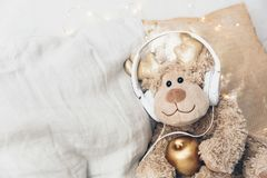 Brown toy with headphones. Cute fun pictures. Listening music Stock Image