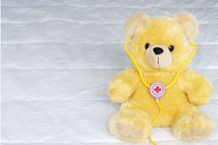 Brown toy soft bear with a phonendoscope on white background childhood concept stock photos