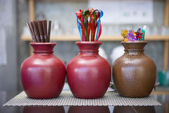 Brown tube and colorful mini spoon in the ceramic vase Royalty Free Stock Image