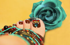 Brown turquoise design pedicure. Beautiful art nail design women's feet in sandals with a rose on a yellow background stock photos
