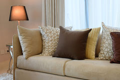Brown tweed sofa with grey patterned pillows Stock Photo