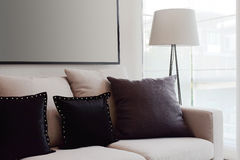Brown tweed sofa with grey pillows and lamp. In living room Stock Photos