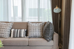 Brown tweed sofa with grey pillows Stock Photography