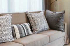 Brown tweed sofa with grey pillows Stock Photos