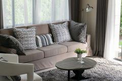 Brown tweed sofa with grey pillows Stock Image