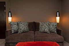 Brown two seated sofa dark ambience. Brown two seated sofa beautiful dark ambience Stock Photos
