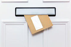 Brown-Umschlag in einem Haustür letterbox Stockbild