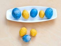 Brown und blaue Muttern, die in Folge auf einer Platte liegen Stockbild