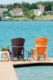 Brown und orange adirondack Stühle auf einem Dock Lizenzfreie Stockfotografie
